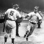 Larry Doby, outfielder for the Cleveland Indians, is congratulated by teammate and manager Lou Boudreau at Fenway Park's home plate after hitting a home run in Boston, Massachusetts on May 10, 1948.